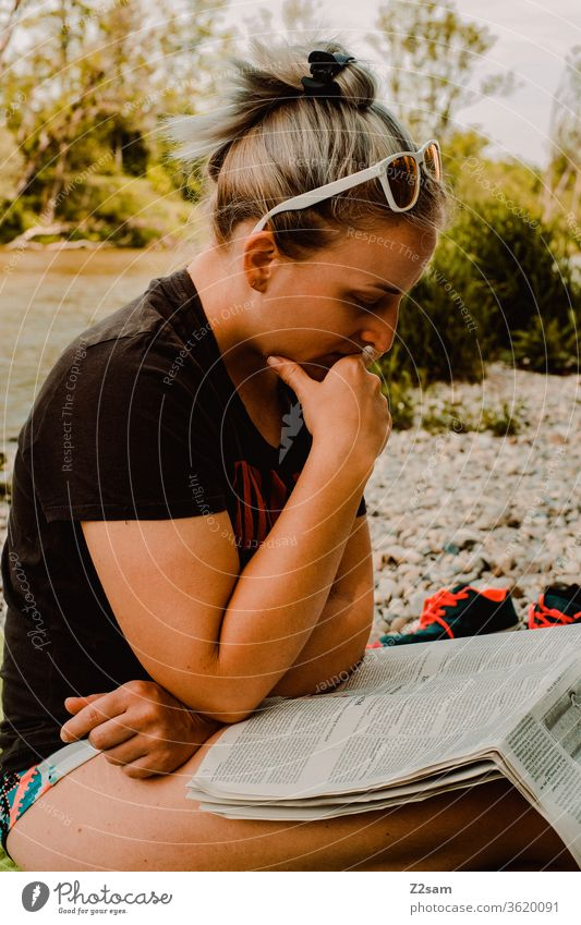 Junge Frau beim Lesen an der Isar isar strand lesen zeitung bildung nachrichten sonnebrille sommer entspannung erholung baden wärme einsam tageszeitung news