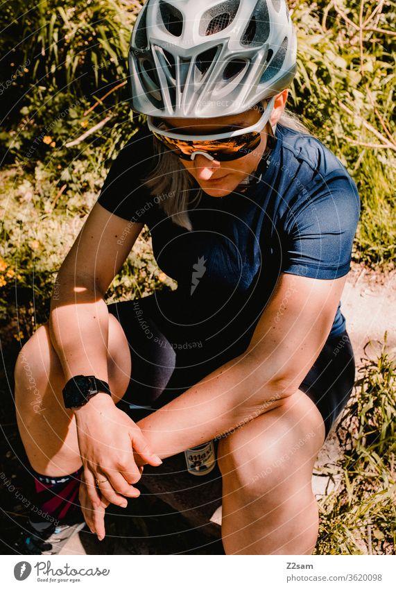 Junge Frau pausiert beim Mountainbiken frau junge frau sport sportlich trikot helm mtb fahrradfahren radsport sonnenbrille mode schutzhelm sitzen wiese ausruhen