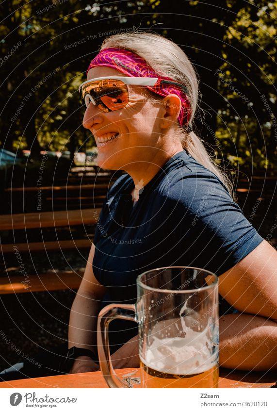 Radtour-Pause im Biergarten bayern biergarten radler trinken genießen entspanne lachen fröhlich glücklich entspannt sportlich trikot sonnebrille junge frau