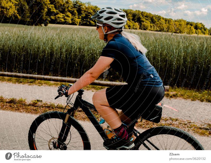 Junge Frau beim Mountainbiken mountainbike fahrrad sport sportlich athlet junge frau spaß bond helm trikot Außenaufnahme Fitness Fahrradfahren Gesundheit