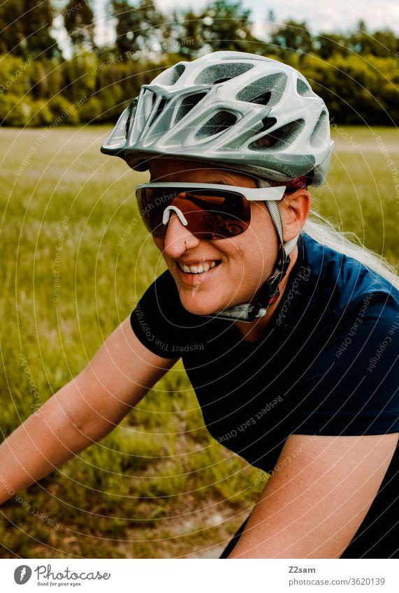 Junge Frau beim Mountainbiken mountainbike fahrrad sport sportlich athlet junge frau spaß hübsch bond sonnebrille helm trikot Außenaufnahme Fitness