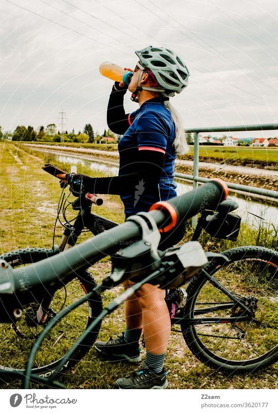 Junge Frau trinkt beim Mountainbiken aus einer Fahrradflasche Sport sportlich Athlet Spaß Schutzhelm Trikot Außenaufnahme Fitness Fahrradfahren Gesundheit