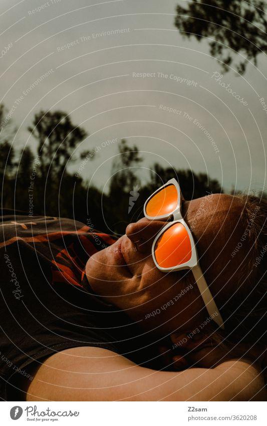 Frau mit Sonnenbrille entspannt in der Abendsonne abendsonne sonnebrille junge frau entspannung urlaub ferien erholung zufriedenheit glücklich