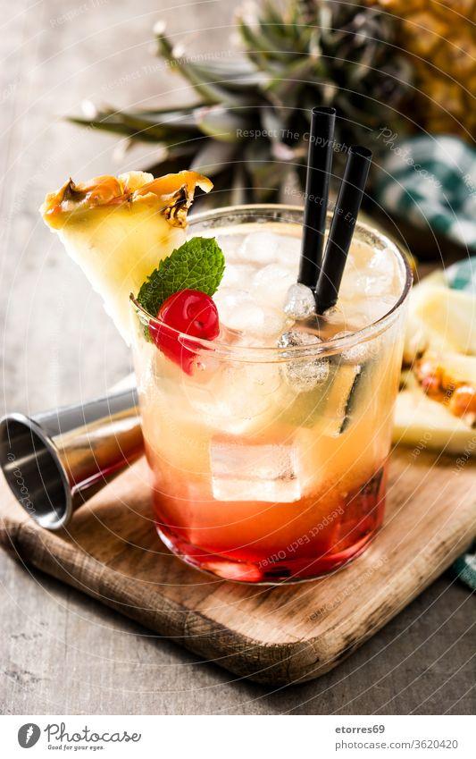 Kalter Mai-Tai-Cocktail mit Ananas und Kirsche auf Holztisch alkoholisch Getränk Schnaps kalt lecker trinken Lebensmittel frisch Frucht Glas Saft Kalk mai tai