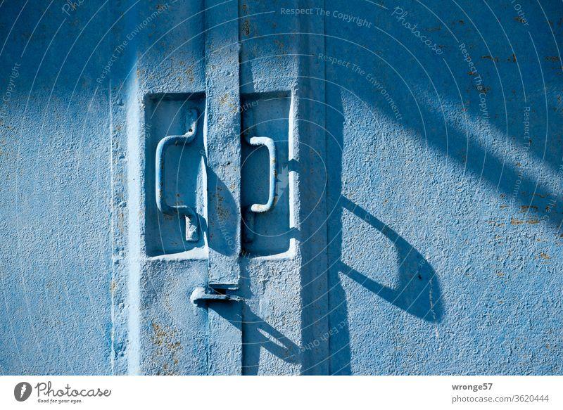 Nahaufnahme zweier Griffe an einem blauen Stahltor Schattenspiel Schattenwurf lange Schatten Tor Garag Garagentor Außenaufnahme Farbfoto Menschenleer Tag