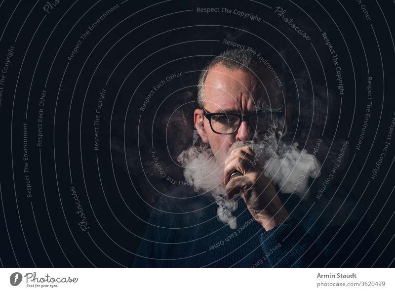 Studioporträt eines Mannes mit Verdampfer und Brille Porträt alt Vollbart grau vaping Rauch Dampf cool ernst E-Zigarette elektronisch vapes männlich Rauchen
