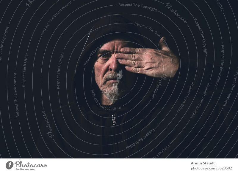 Porträt eines Mannes mit Kapuzenpulli, der eine Hand vor dem Auge hält blind sehen Halt Deckung Finger Vollbart grau Glas schwarz dunkel ernst Gefahr intensiv
