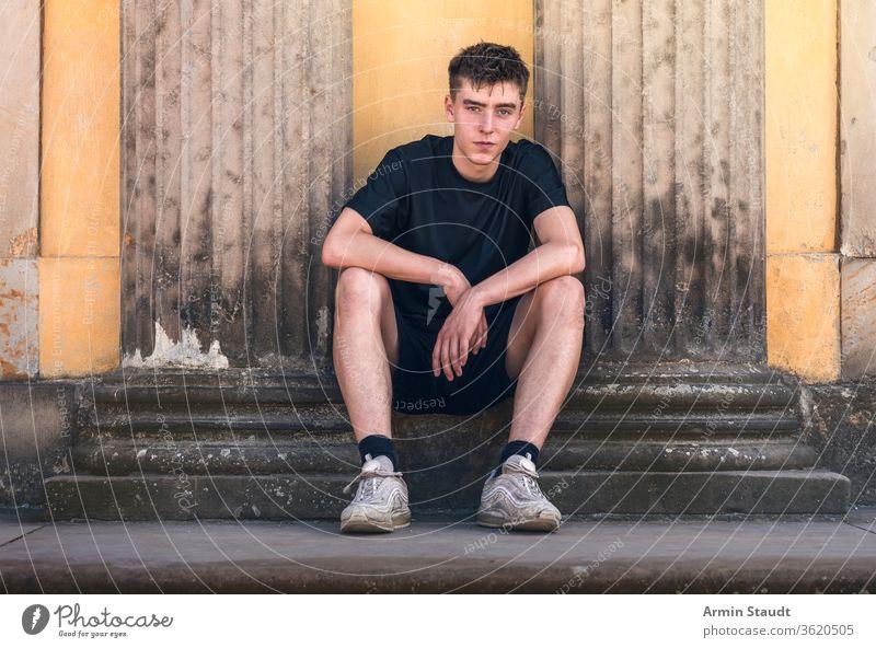 Porträt eines jungen Mannes, der zwischen zwei antiken Säulen sitzt Sitzen Historie Lächeln selbstbewusst im Freien Sommer Grunge alt gutaussehend Teenager