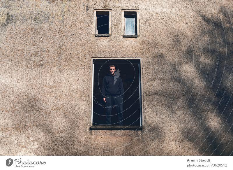Lächelnder junger Mann steht in einem offenen Fenster eines Hauses Stehen alt Ruine Blick weit breit Hand Entfernung schwarz Architektur Gebäude Verlassen antik