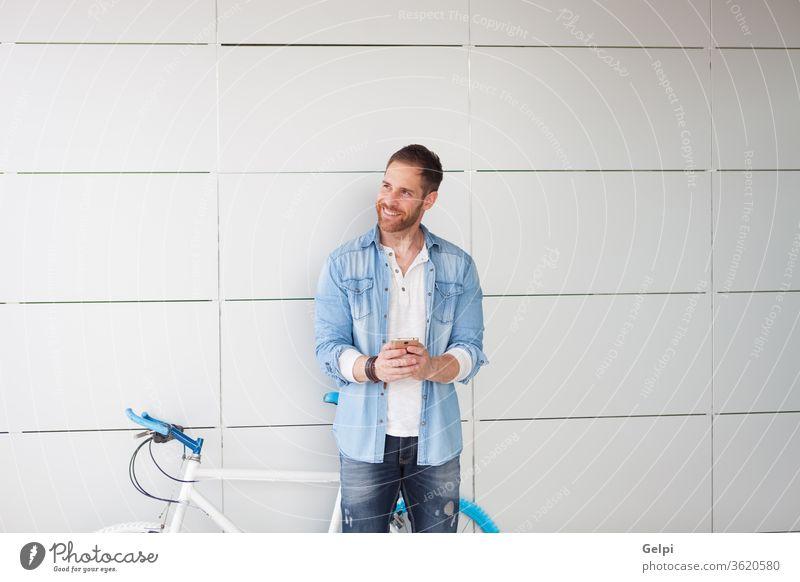 Lässiger Typ neben einem Oldtimer-Fahrrad mit dem Handy Telefon jung Mann Mobile urban Lifestyle Person männlich Großstadt im Freien Hipster Zelle