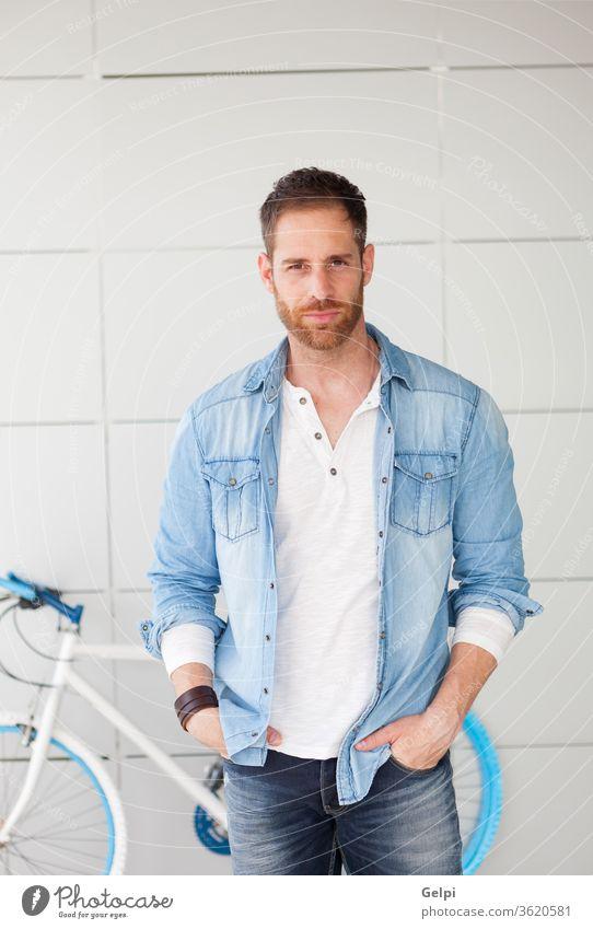 Lässiger Typ neben seinem Fahrrad, der in die Kamera schaut Hipster Lifestyle urban jung Mann Hintergrund gutaussehend männlich lässig blau besinnlich Denken