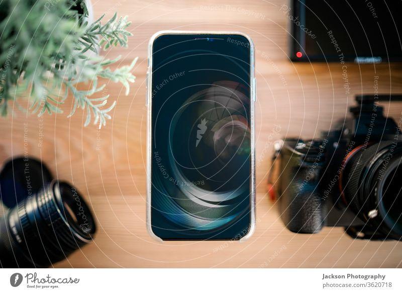 Draufsicht auf Smartphone, dslr-Kamera und Objektiv auf Holzschreibtisch Telefon Fotokamera Fotografie Technik & Technologie Business Desktop hölzern Blume