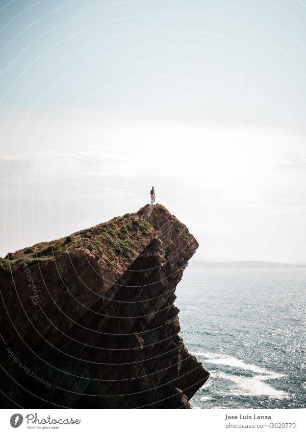 Silhouette einer Person auf der Spitze einer Meeresklippe Abenteuer extrem Natur hoch Felsen Erfolg Freiheit frei Himmel Mann Berge u. Gebirge Sonne Klippe