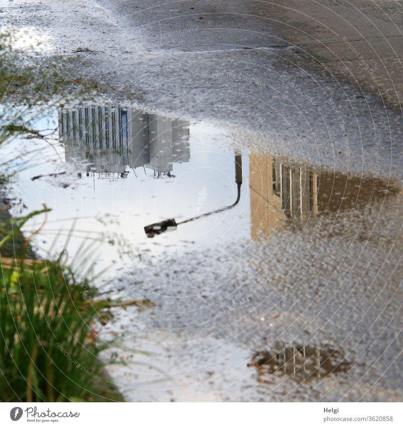 Spiegelung von Gebäuden und einer Straßenlaterne in einer Pfütze auf dem Asphalt Reflexion Hochhaus Laterne Gras Sonnenlicht Wasser Regen nass