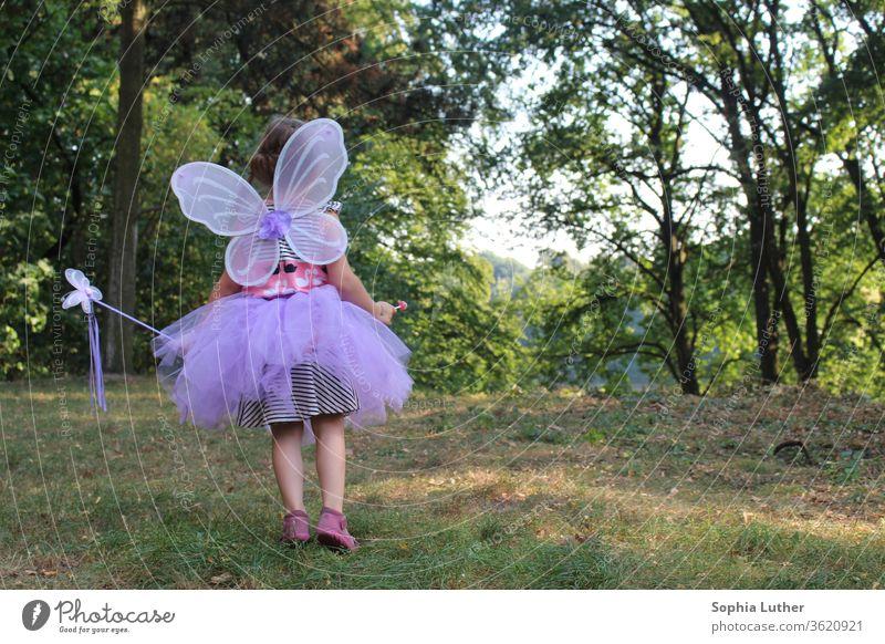 Mädchen im Feenkostüm / verkleidetes Mädchen Kind Fee mädchenhaft feenhaft Außenaufnahme Kindheit Farbfoto feminin schön Lichtung Kleid Tutu Blick Wiese Sommer