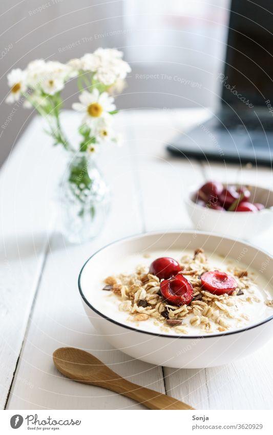 Müsli mit Joghurt und Kirschen auf einem weißen Holztisch und ein Laptop. Gesundes Frühstück. Haferflocken Schalen & Schüsseln laptop Holztür Homeoffice