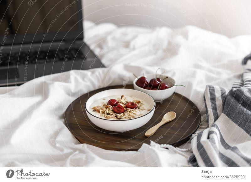 Joghurt mit Müsli und Kirschen auf einer weißen Bettdecke und ein Laptop Frühstück Schlafzimmer laptop Homeoffice Frucht Schüsseln Dessert Hafer organisch