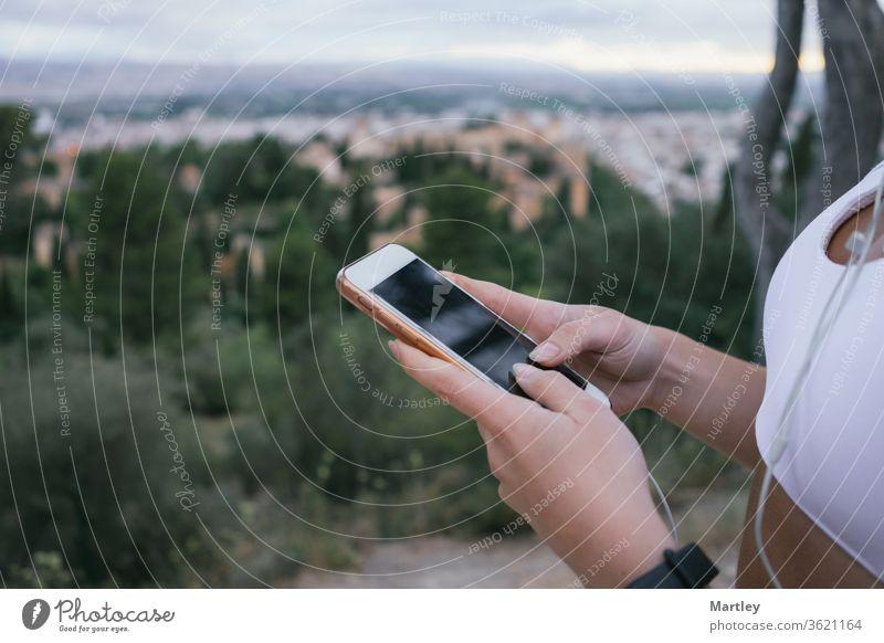 Hände eines jungen Mädchens beim Telefonieren in der Natur nach dem Sport. Beschneiden Sie eine ierkannte Frau mit der mobilen Tracking-App, während sie im Freien trainiert.