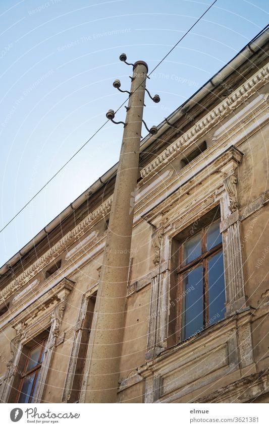 Teilansicht eines maroden Gebäudes aus der Gründerzeit mit hohen Fenstern aus der Froschperspektive und mit einem alten Strommast davor altes Gebäude wohnen