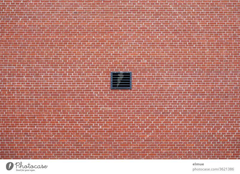 kleines quadratisches, schwarzes Lüftungsfenster in einer roten, der Ziegelbauweise nachempfundenen Fassade Wand Mittelpunkt Geometrie Kunststoff
