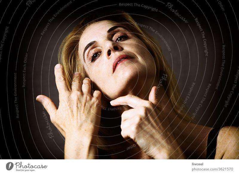 reife Schönheit, die mit den Händen nahe am Gesicht gestikuliert Porträt Frau Menschen eine Person gestikulierend schön reif blondes Haar grünlicher Hintergrund