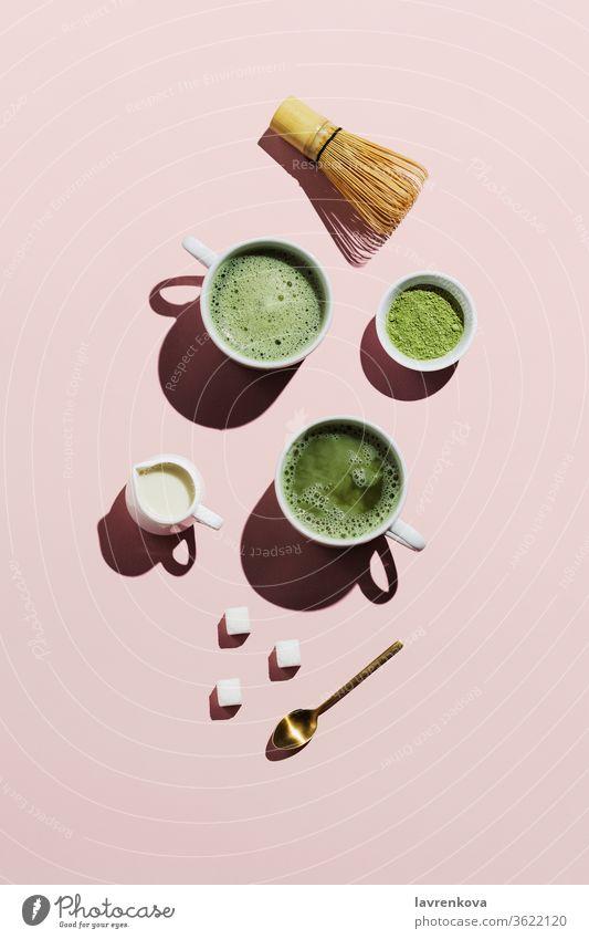 Veganer Matcha Latte mit Hafermilch auf rosa Pulver Schneebesen Milchkännchen Zucker Würfel Tasse Tee Japanisch Becher Getränk trinken Erfrischungen heiß