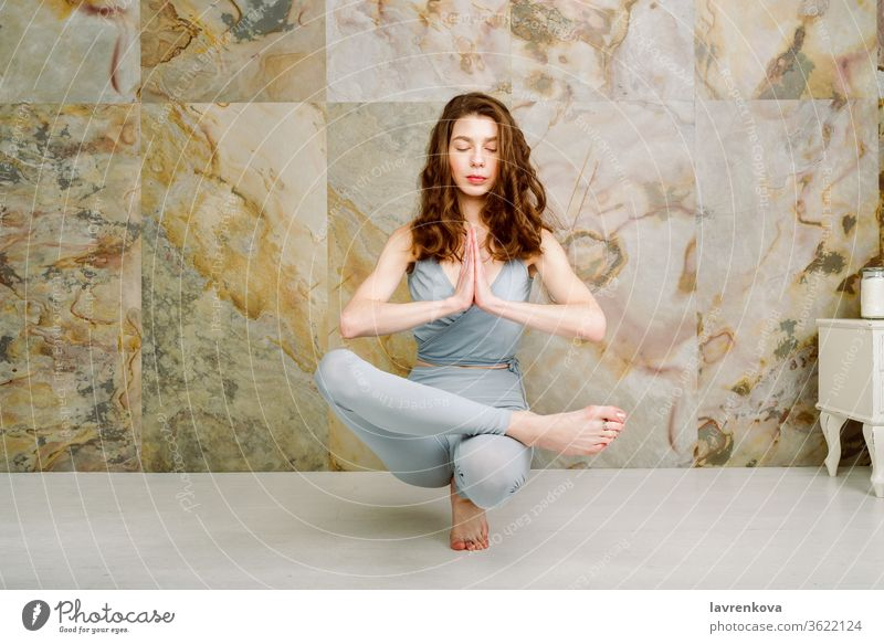 Junge Frau übt Zehenstand (Padangusthasana) Posieren im Haus, selektiver Fokus Yoga Training Sport aktiv yogini Asana sportlich schlank dünn im Innenbereich