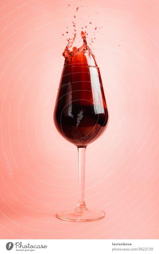 Rotweinspritzer im Glas, dynamisches Bild, selektiver Fokus. Wein Schnaps Gießen Tröpfchen liquide Weingut rot Getränk trinken Feier Alkohol rosa Bewegung
