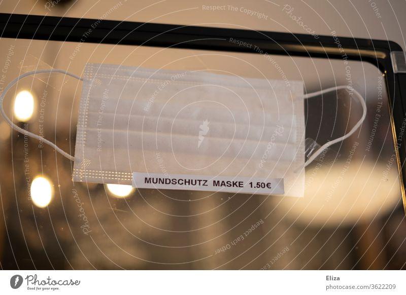 Eine Trennwand aus Plexiglas an der ein Schild auf den Verkauf von Mundschutz und Maske hinweist Geschäft Schutz Corona Gewinn Verkaufen Profit Laden anbieten
