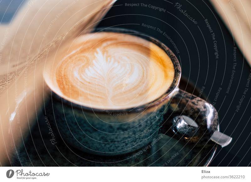 Ein Cappuccino mit einer Zeitung. Morgenroutine. Latte Art Kaffee morgens Kaffeetrinken Zeitunglesen Café Tageszeitung Kaffeetasse Tasse Kaffeepause