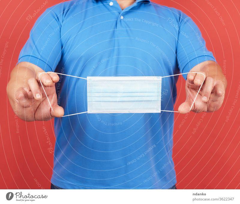 Mann mit blauem T-Shirt hält einen Stapel weißer medizinischer Einweg-Gesichtsmasken Mundschutz Medizin Menschen Person Prävention behüten Schutz Quarantäne rot