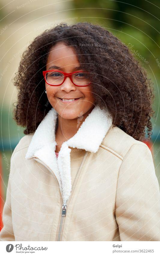 Afrikanisches Mädchen mit schönem Haar in einem Park Kind zehn Amerikaner hübsch Behaarung Schule Porträt Gesicht Vielfalt jung Afro-Look Schönheit Himmel