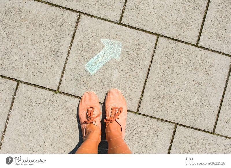 Füße stehen vor einem grünen Pfeil, der mit Kreide auf den Boden gemalt ist. Wegweiser, Richtung, Entscheidungshilfe. richtig Orientierung Zeichen Navigation