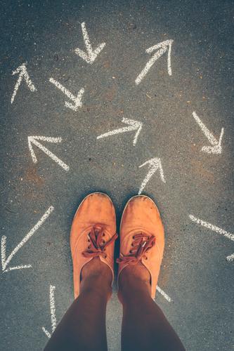 Ein Paar Füße umgeben von Pfeilen, die in verschiedene Richtungen zeigen. Konzept Orientierungslosigkeit, Verwirrung und Unentschlossenheit. verwirrt