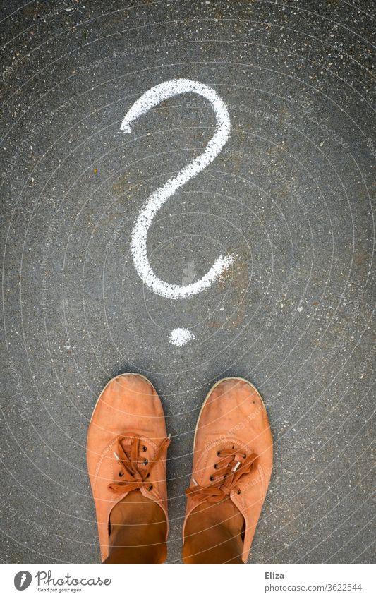 Füße stehen vor einem Fragezeichen, das mit Kreide auf den Boden gemalt ist. Frage, Ratlosigkeit, Unentschlossenheit. Entscheidung ratlos Verwirrung