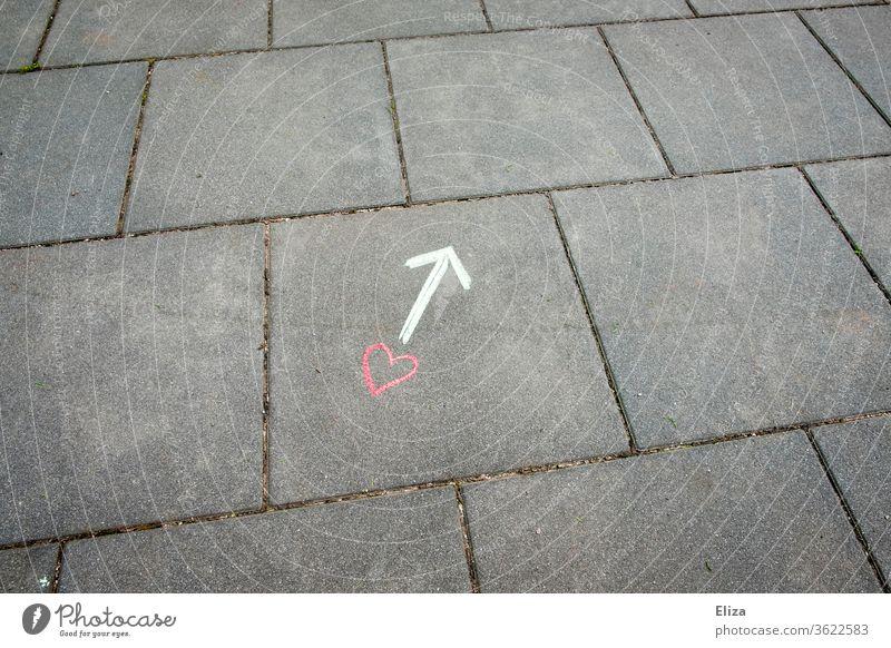 Ein Herz und ein Pfeil mit Kreide auf dem Boden gezeichnet Liebe Beziehung Wegweiser Richtung Gefühle Liebesleben Suche finden Zeichnung Konzept auf der Suche