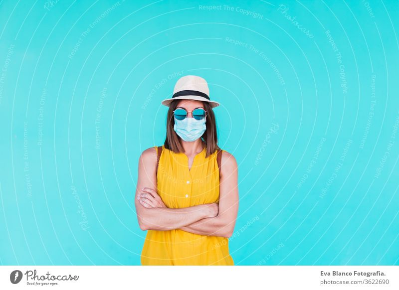 Porträt einer jungen Frau im Freien vor türkisfarbenem Hintergrund mit Schutzmaske. Sommerzeit und Coronavirus-Konzept Corona-Virus Türkisfarbener Hintergrund