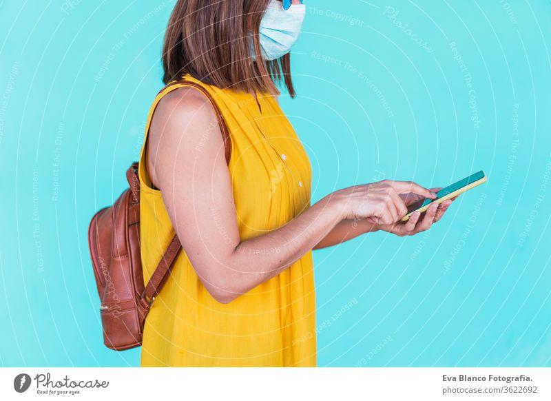 Porträt einer jungen Frau im Freien vor türkisfarbenem Hintergrund mit Schutzmaske. Mit Mobiltelefon. Sommerzeit und Coronavirus-Konzept Handy