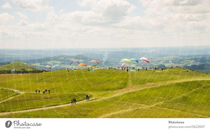 Bunte Gleitschirmflieger auf der Wasserkuppe Außenaufnahme Tag Glück Smiley fliegen Freude Luftverkehr Wolkenloser Himmel Sommer Freiheit Ferne Abenteuer