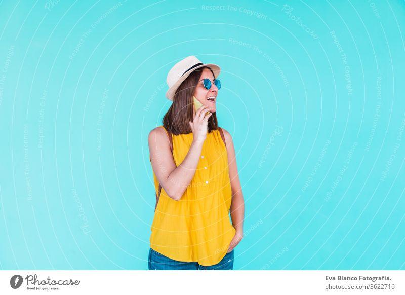 junge Frau, die im Freien vor einem türkisfarbenen Hintergrund mobil telefoniert. Sommerzeit Handy Türkisfarbener Hintergrund Sonnenbrille gelb Hut Rucksack