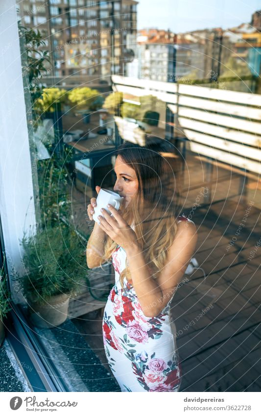Frau trinkt Kaffee, während sie die Ansichten beobachtet Blick durch das Glas Fenster trinken Getränk Pause Reflexion & Spiegelung die Ansichten beobachten Tee
