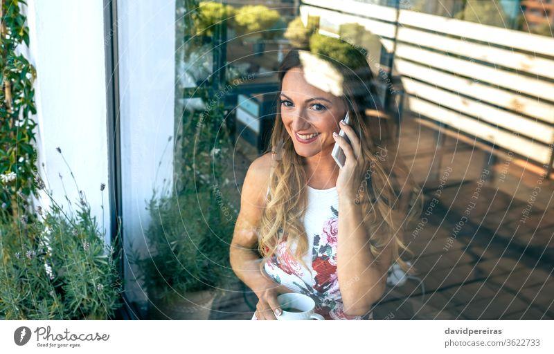 Frau am Handy mit Kaffeetasse sprechend durch das Glas Reflexion & Spiegelung Fenster Getränk die Ansichten beobachten Pause Tee Blick elegant Glück Mobile