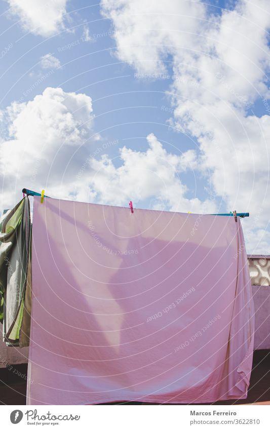 Kleider, die auf der Terrasse in der Sonne hängen. Himmel mit Sonne und Wolken im Sommer Wäscheklammer Konzept Stifte im Freien außerhalb Sonnenlicht luftfrei
