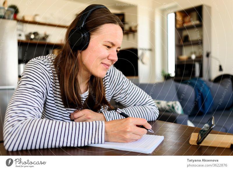 Frau mit Kopfhörern lernt zu Hause Bildung online Lernen E-Learning heimwärts Entfernung zuschauend hören Schüler Hausaufgabe Internet studierend