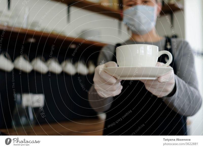 Kellnerin mit Becher in Gesichtsmaske und Handschuhen Kaffee Tasse Frau Café Restaurant Dienst Schürze schützend trinken Job Kantine Werkstatt Arbeiter Personal