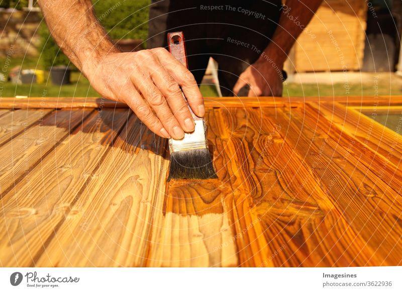 Lasieren. Holzarbeiten, streichen von Holz. Hand des Handwerkers, der eine Holztür lackiert. Konzept der Renovierungsarbeiten, Zimmerei  und Holzarbeiten. Maler, der Holzoberfläche malt, Holzschutz