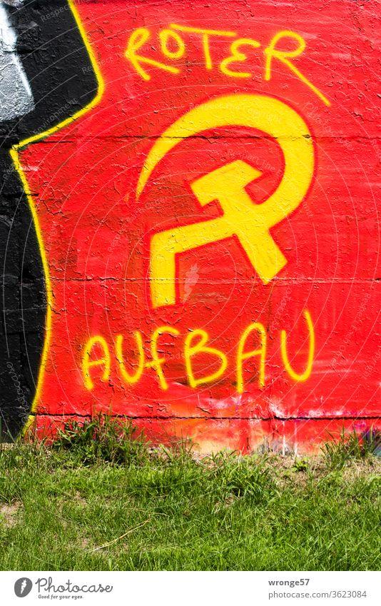 Graffiti Hammer und Sichel mit gelber Farbe auf roten Untergrund an eine Mauer gesprüht und mit den Worten Roter Aufbau ergänzt gelbe Farbe roter Untergrund