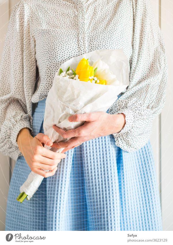Frau hält Tulpenstrauß. Der Tag der Frau Blume Haufen Mutter geben Frühling Ostern Hände geblümt weiß gelb Dame März Geschenk Einladung Gruß Postkarte