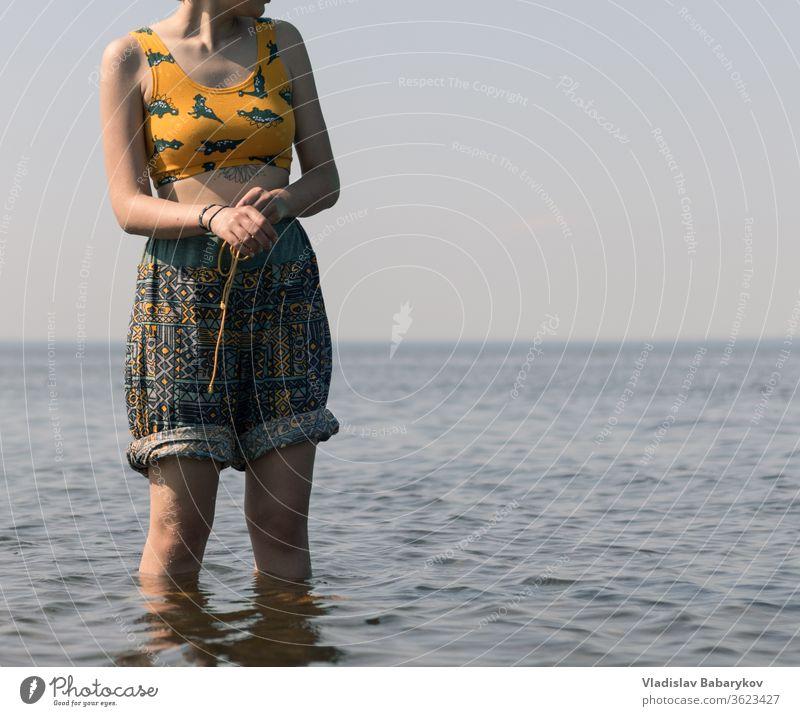 Junge Frauen mit einer Tätowierung stehen im Wasser Mädchen Tattoo MEER Seeküste