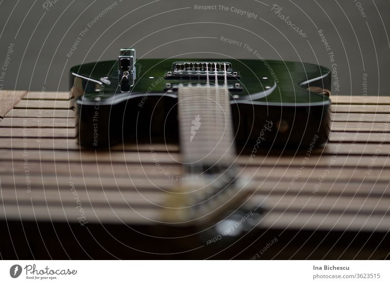 Eine schwarze E-Gitarre auf einem Holzbrett-Tisch fotografiert aus der Gitarren Kopf Perspektive. Der Fokus liegt am Seitenhalter und Knopf. Egitarre